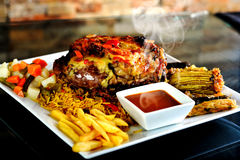 Grilled bbq steak with rosemary. Meat Grilled bbq steak with rosemary with potato and appetizer and yellow rice Royalty Free Stock Images