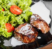 Grilled beaf steak meat with fresh vegetable salad and tomatoes. On black plate, wooden background. Hot Meat Dishes stock photo