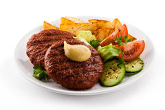Grilled beef. Grilled meat with baked potatoes and vegetable salad royalty free stock photos