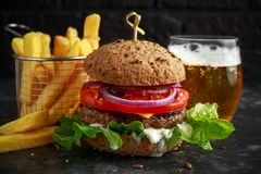 Grilled beef burger with lettuce, greek yogurt souce, beef tomatoes, red onion rings and melted cheese served with. Potato fries and cold beer on a rustic stock images