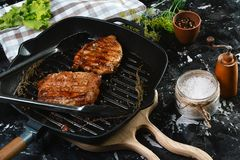 Grilled beef fillet steaks with herbs and spices on dark background. Food concept stock images