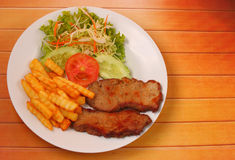 Grilled beef and french fries thai style. On a wood table top Stock Photo