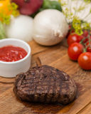 Grilled beef with garnish on wooden board Royalty Free Stock Photography