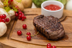 Grilled beef with garnish on wooden board Stock Photo