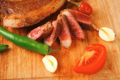 Grilled beef meat fillet sliced on wood. Fresh grilled beef meat fillet sliced on wooden board with tomatoes and red pepper and cutlery isolated  over white Stock Images
