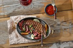 Grilled beef meat pan table sauce red wine top view. Grilled beef meat served in a frying pan on wooden table with sauce and glass of red wine, top view royalty free stock photos