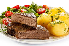 Grilled beef. Grilled meat with roasted potatoes and vegetable salad royalty free stock photo