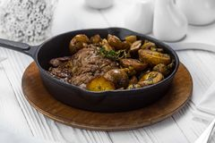 Grilled beef meat steak with fried potatoes royalty free stock images