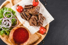 Grilled beef meat and vegetables with fresh salad and bbq sauce on cutting board over black stone background. Hot Meat Dishes stock photography