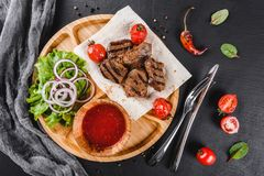 Grilled beef meat and vegetables with fresh salad and bbq sauce on cutting board over black stone background. Hot Meat Dishes royalty free stock photos