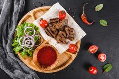 Grilled beef meat and vegetables with fresh salad and bbq sauce on cutting board over black stone background royalty free stock images