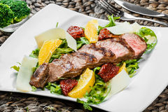 Grilled beef with orange fruit, arugula, parmesan cheese and sun-dried tomatoes on bamboo background. Traditional meat for Holidays. Top view Royalty Free Stock Photo