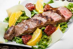 Grilled beef with orange fruit, arugula, parmesan cheese and sun-dried tomatoes on bamboo background. Traditional meat for Holidays. Top view Royalty Free Stock Photography