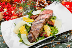 Grilled beef with orange fruit, arugula, parmesan cheese and sun-dried tomatoes on Christmas background with light. Traditional meat for Holidays. Top view Royalty Free Stock Photos