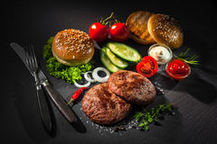 Grilled beef patties with other ingredients for hamburgers Royalty Free Stock Photos