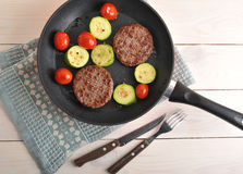 Grilled beef patties with zucchini and cherry tomatoes in the pa Royalty Free Stock Images