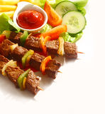 Grilled beef and pepper kebabs. High angle view of three grilled beef and sweet pepper kebabs served with a dish of tomato ketchup, potato chips and fresh salad Stock Photos
