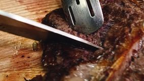 Grilled beef pork meat steak fillet with asparagus hot red peppers and cutlery on wooden cutting plate over wooden table. 4K resolution stock footage