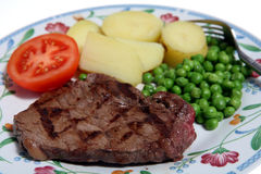 Grilled beef rump steak potato. A meal of grilled rump steak, peas, boiled potatoes and tomato Stock Image
