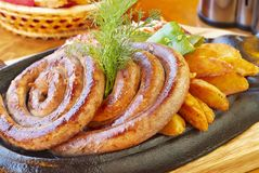 Grilled beef sausage with roasted potatoes Royalty Free Stock Photo
