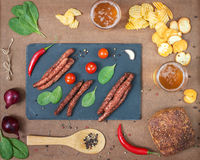 Grilled beef sausages with beer and snacks. Stock Photos