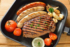 Grilled beef and sausages Stock Images