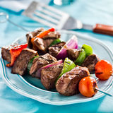 Grilled beef shishkabobs on table Royalty Free Stock Images
