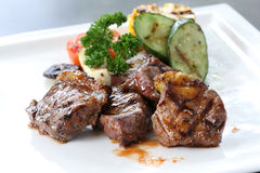 Grilled beef sirloin with roasted vegetables on white dish Stock Photos