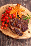 Grilled Beef Sirloin Steak on wooden board with vegetables. Stock Photography