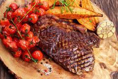 Grilled Beef Sirloin Steak on wooden board with vegetables. Royalty Free Stock Image