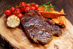 Grilled Beef Sirloin Steak on wooden board with vegetables. Stock Photo