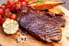 Grilled Beef Sirloin Steak on wooden board with vegetables. Stock Photos