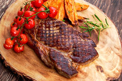 Grilled Beef Sirloin Steak on wooden board with vegetables. Royalty Free Stock Photos