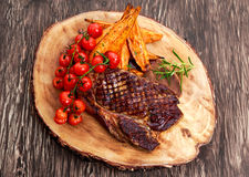 Grilled Beef Sirloin Steak on wooden board with vegetables. Stock Images
