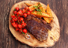 Grilled Beef Sirloin Steak on wooden board with vegetables. Royalty Free Stock Images