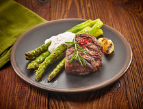Grilled beef steak and asparagus on dark plate Stock Photography