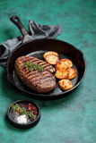 Grilled beef steak and baked potato in cast iron skillet Royalty Free Stock Photos