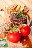 Grilled beef steak, baked potatoes and vegetable on wooden bread Royalty Free Stock Images