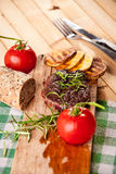 Grilled beef steak, baked potatoes and vegetable on wooden bread Royalty Free Stock Photo