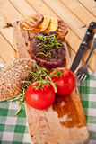 Grilled beef steak, baked potatoes and vegetable on wooden bread Stock Photo