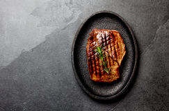 Grilled beef steak on black cast iron plate. Background with copy space. Barbecue, bbq meat beef tenderloin. Top view. Slate background royalty free stock photos