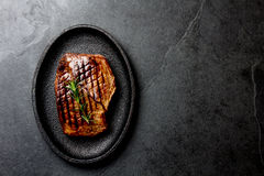 Grilled beef steak on black cast iron plate. Background with copy space. Barbecue, bbq meat beef tenderloin. Top view. Slate background royalty free stock image