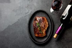 Grilled beef steak on black cast iron plate with red wine. Background with copy space. Barbecue, bbq meat beef tenderloin. Top vie. W, slate background stock images