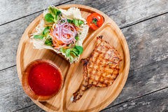 Grilled beef steak on bone, fresh salad, grilled vegetables and tomato sauce on cutting board on wooden background Royalty Free Stock Photos