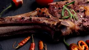 Grilled beef steak on bone with tomatoes stock video