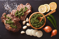 Grilled beef steak with chimichurri sauce on slate board. Horizo stock photo