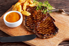 Grilled Beef Steak with Chips and Mango souce on wooden board. Grilled Beef Steak with Chips and Mango souce on wooden board Stock Photography
