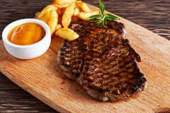 Grilled Beef Steak with Chips and Mango souce on wooden board. Grilled Beef Steak with Chips and Mango souce on wooden board Royalty Free Stock Photo