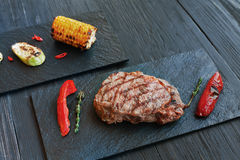Grilled beef steak closeup on dark wooden table background Stock Photo
