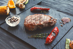 Grilled beef steak closeup on dark wooden table background Stock Images